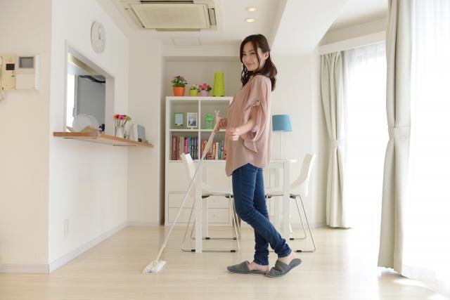 マンションリビングのフローリングを掃除する女性