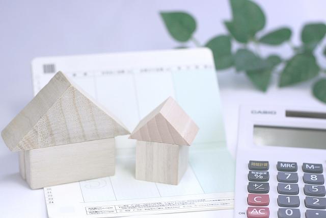 住宅ローンのイメージ(家と電卓、通帳)