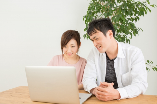 夫婦がパソコンで住宅ローンについて調べている